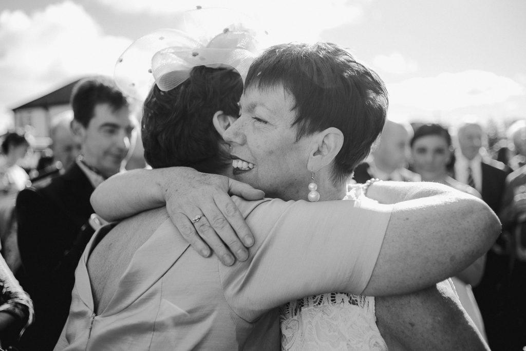 two weddings guests hugging