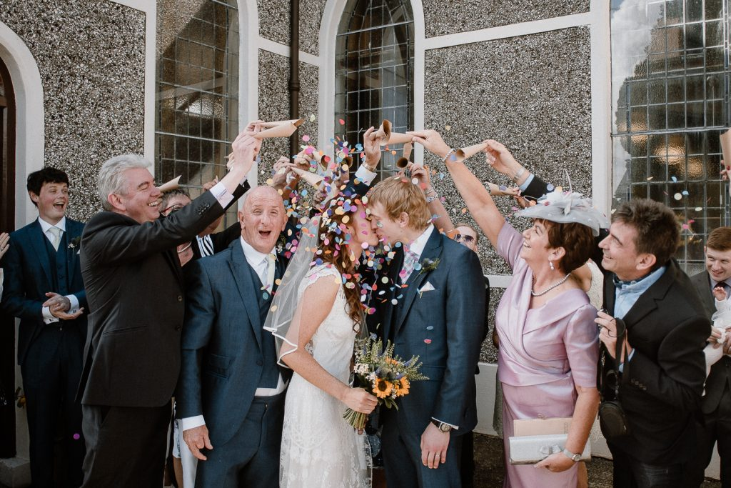 guests throw coloured confetti over bride and groom