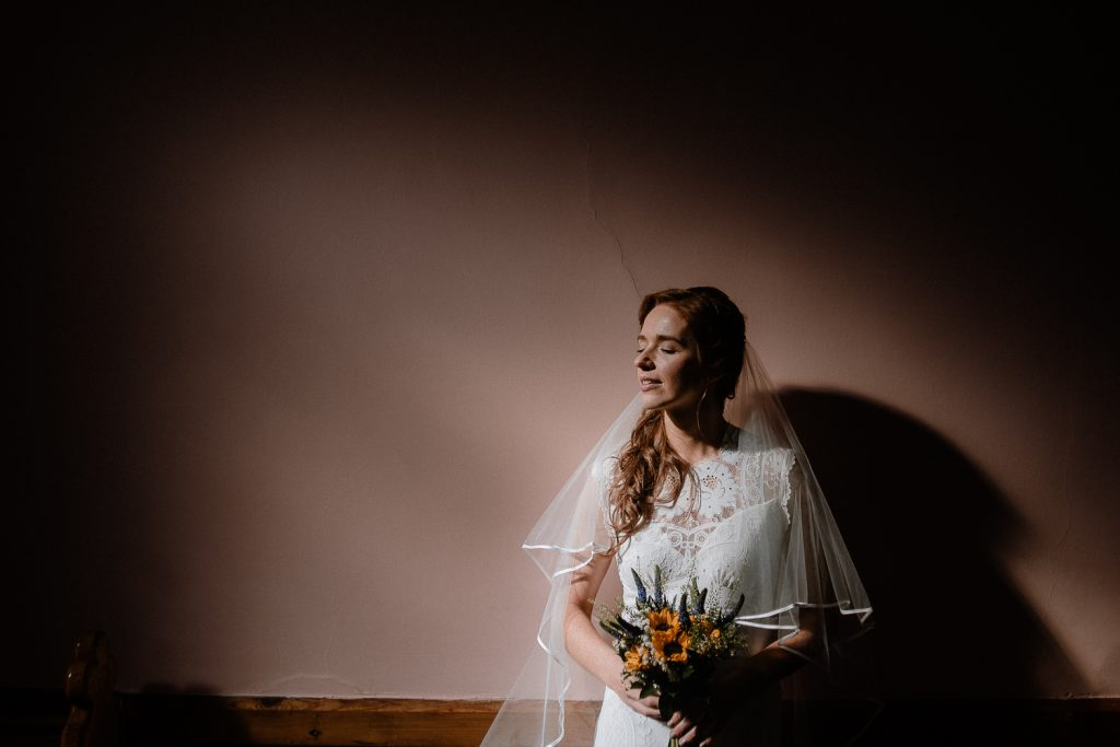 bride standing in light in church