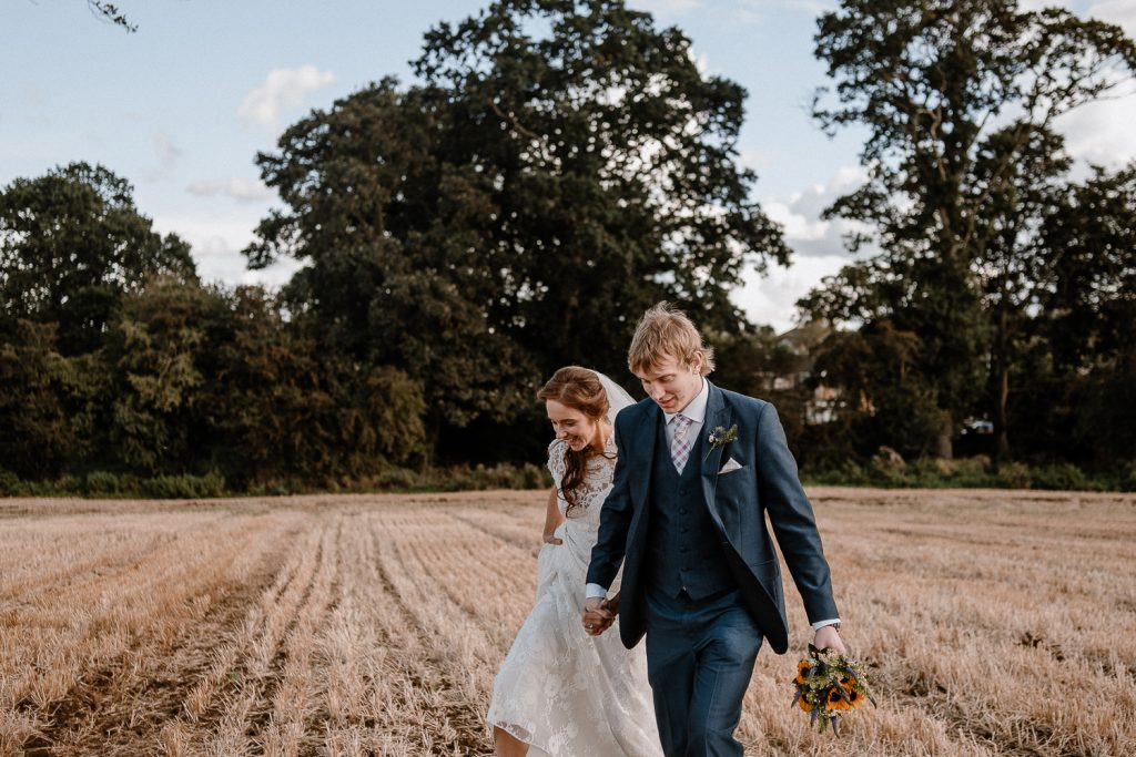 bride and groom walking into a field