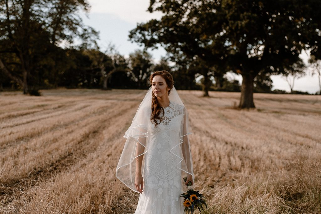bride stands alone in field. Gracehall wedding