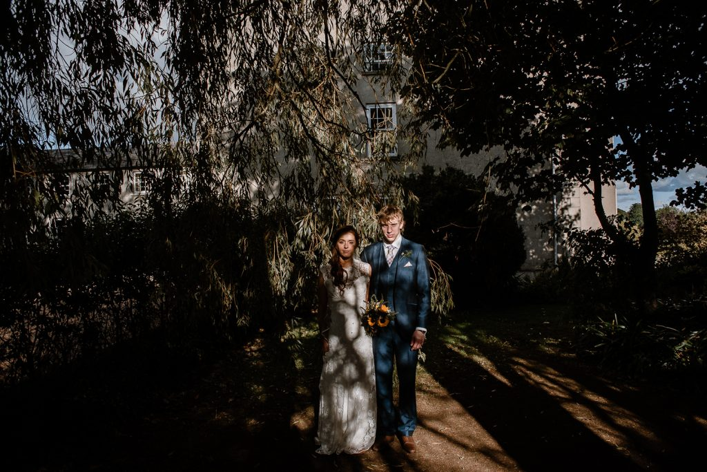 bride and groom standing among shadows and lights
