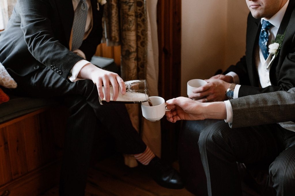 groomsman pouring beer into tea cup