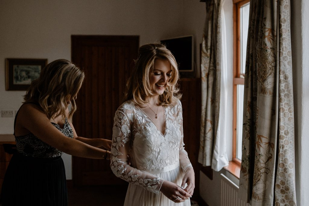 bride smiling as her sister buttons back of dress