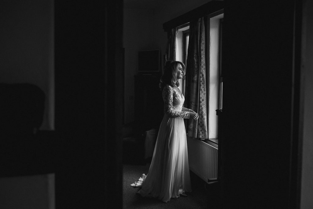 bride standing alone in wedding dress in soft window light