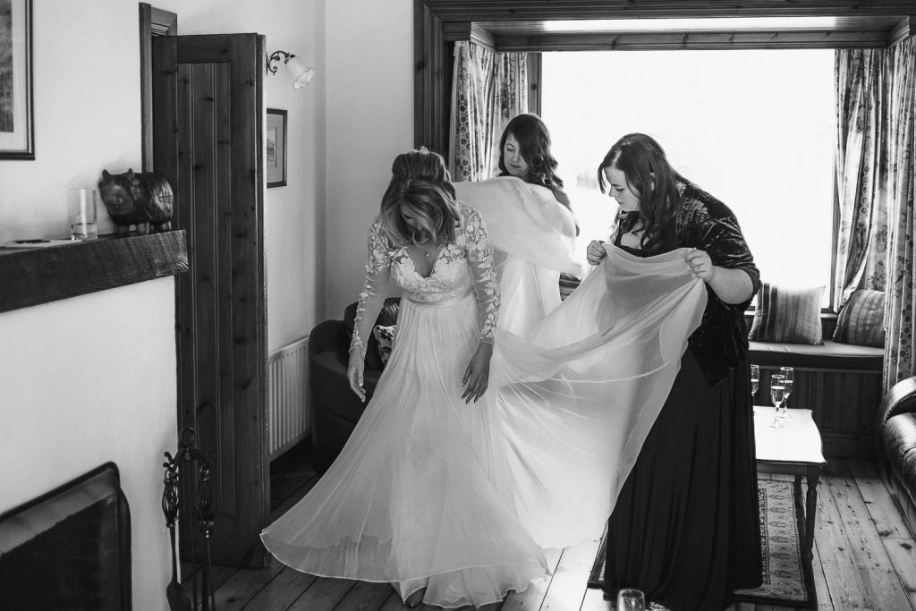 bridesmaids fixing brides dress