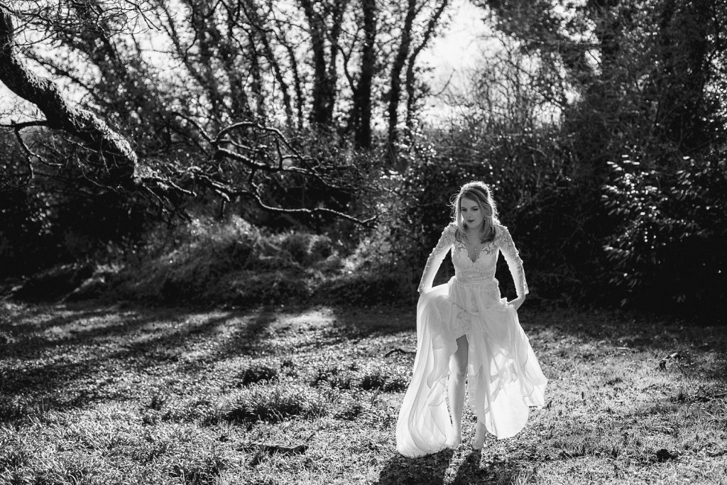 bride lifting her dress to walk though a muddy field