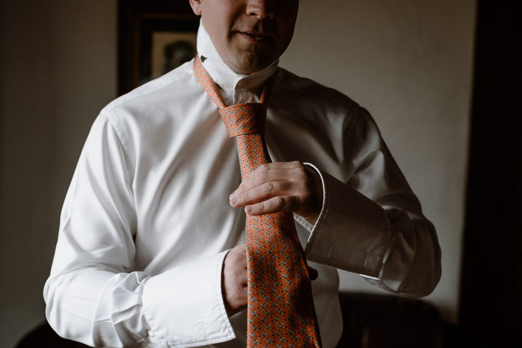 close up of groom doing tie