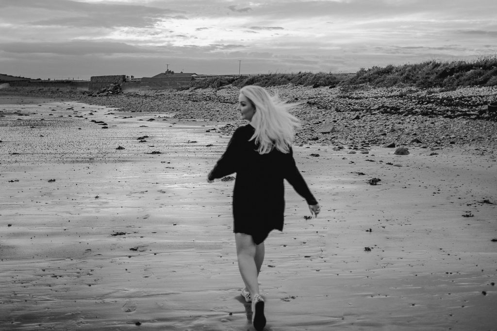 woman with blond hair and black dress running on beach