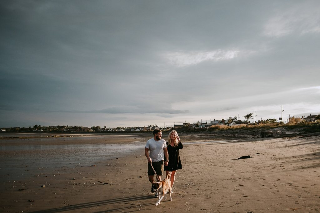 couple walking on beach with dog at sunset