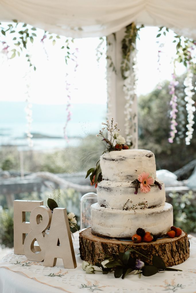wedding cake sitting on a wooden log