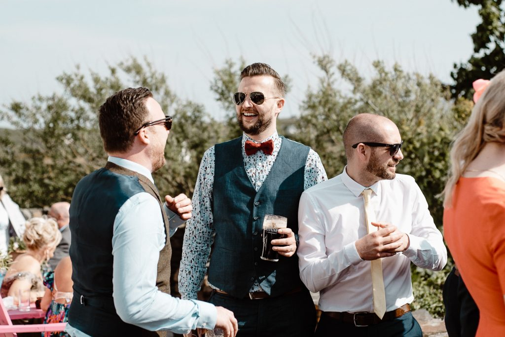 man in bowtie holding beer