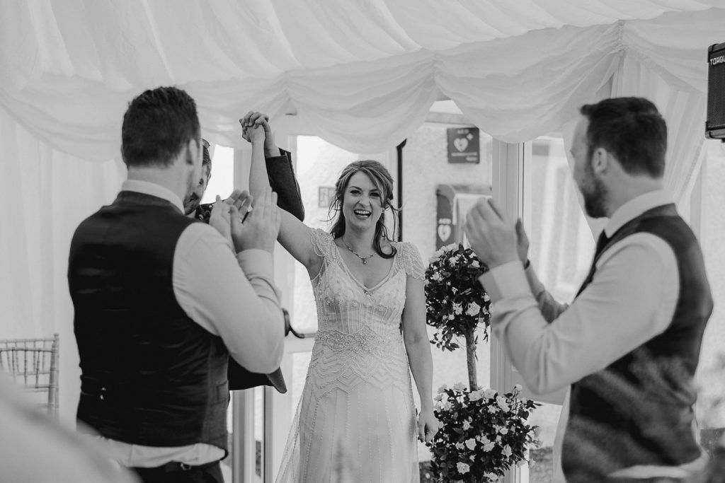 bride smiling and holding hand in the air