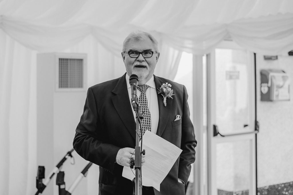 man wearing shirt and tie with glasses give a speech