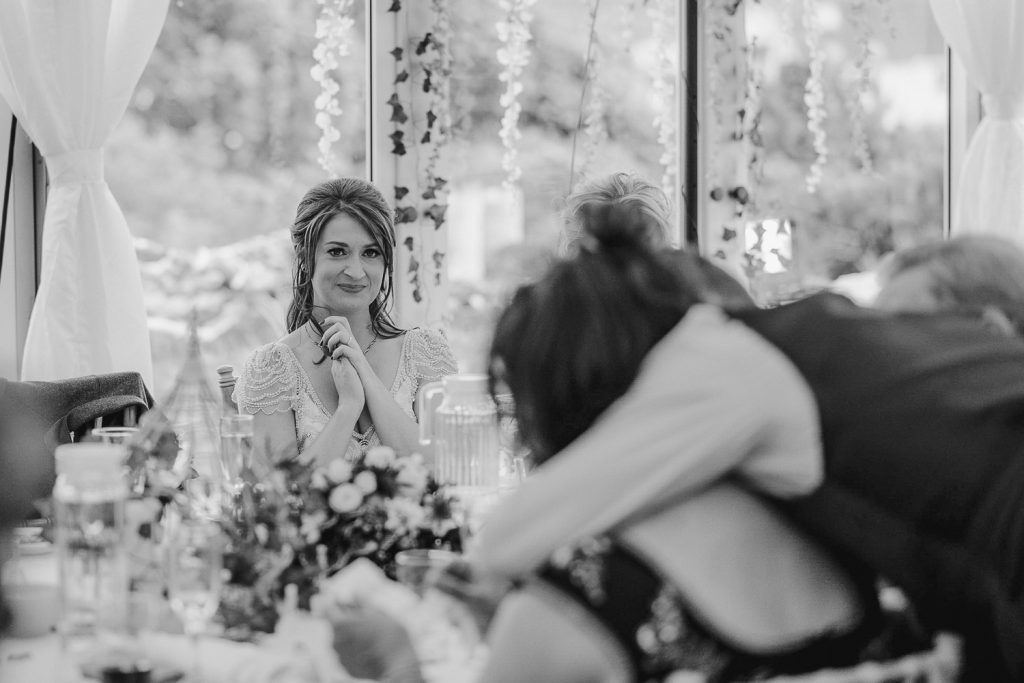 bride looks on as groom hugs his mother