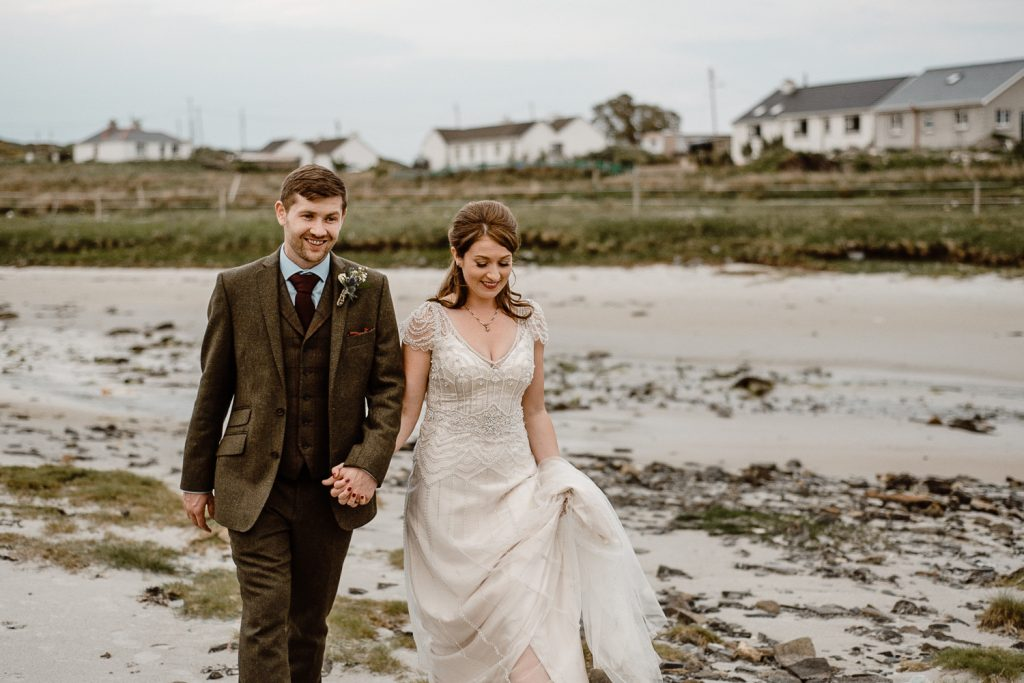 bride and groom holding hands walking on beech behind dawros bay house donegal