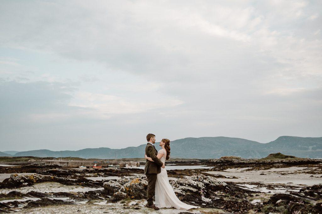 bead and groom facing each other on beach