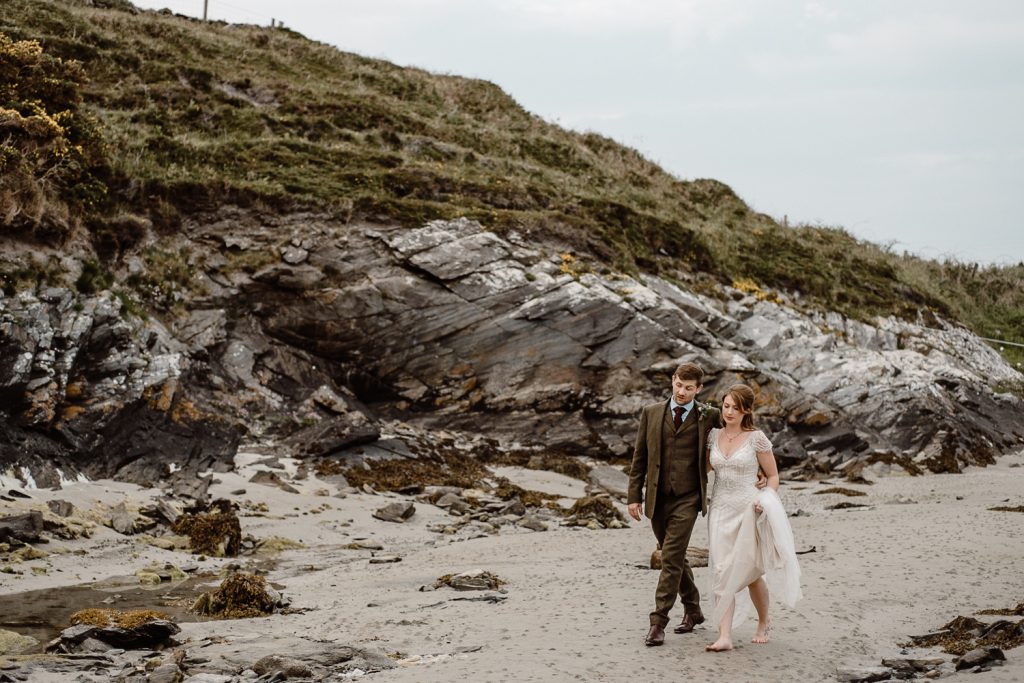 bride and groom walking on beach in donegal