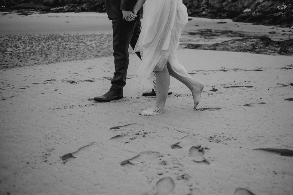 close up of bride walking barefoot on sand