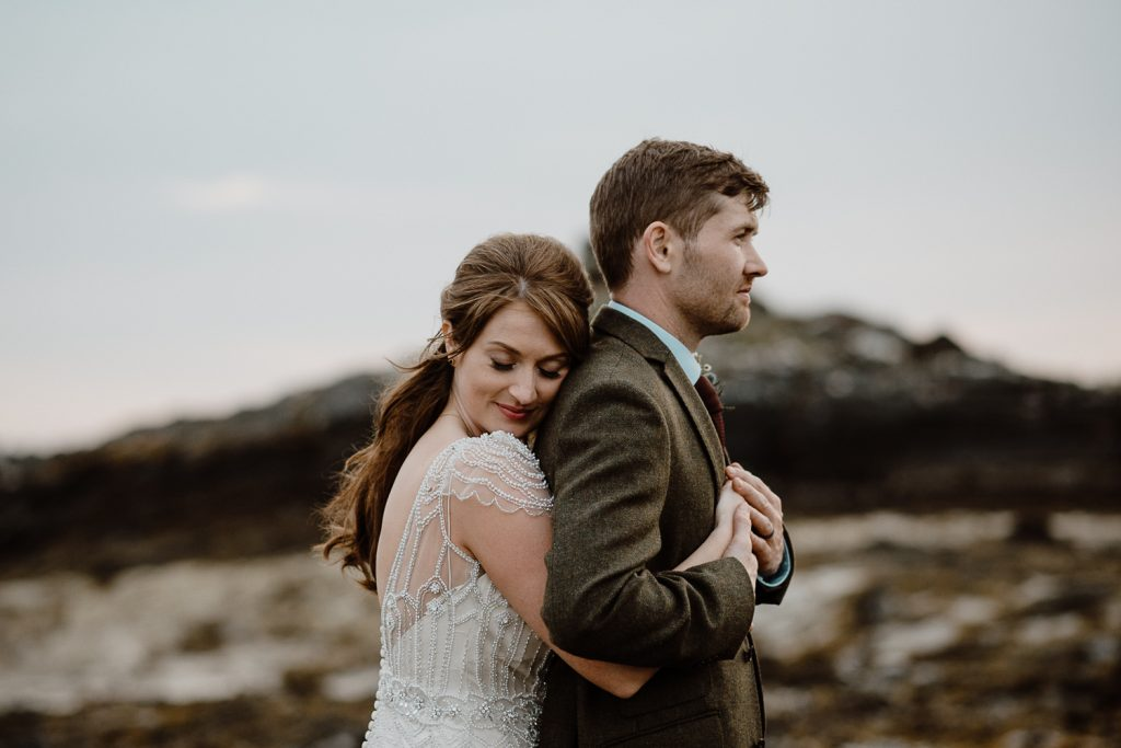 close up of bride hugging into grooms back