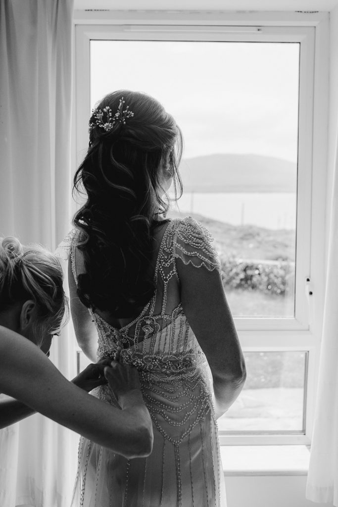bride getting back of dress zipped at window