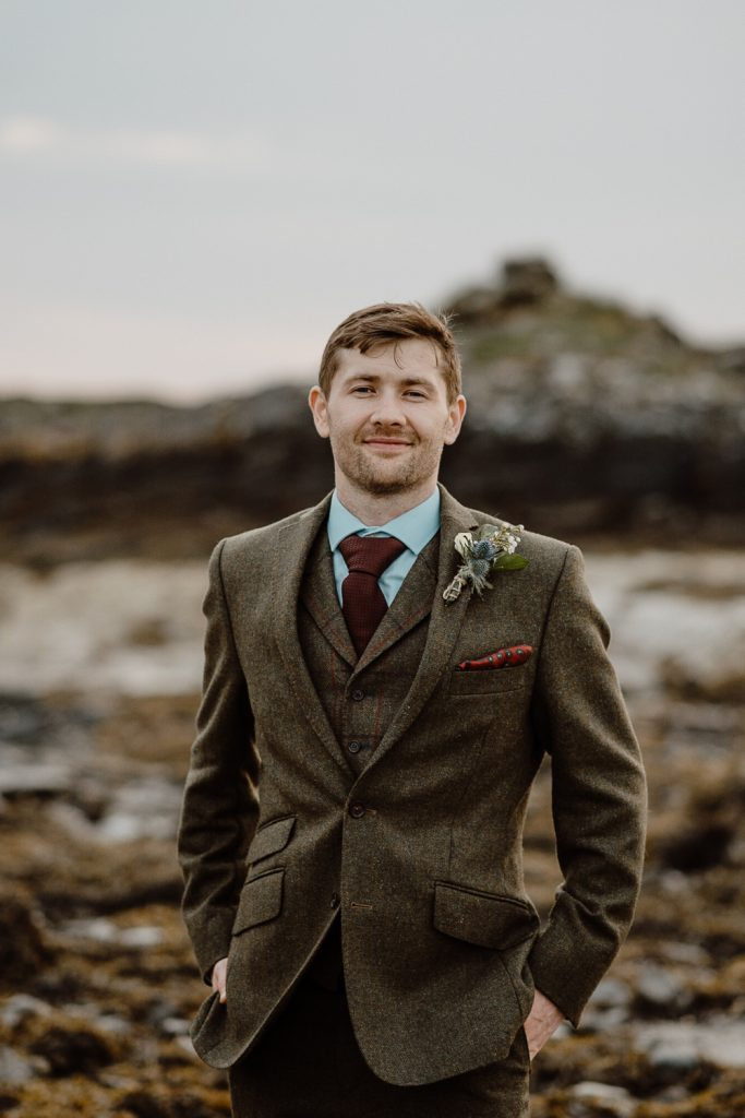groom smiling with hands in pockets