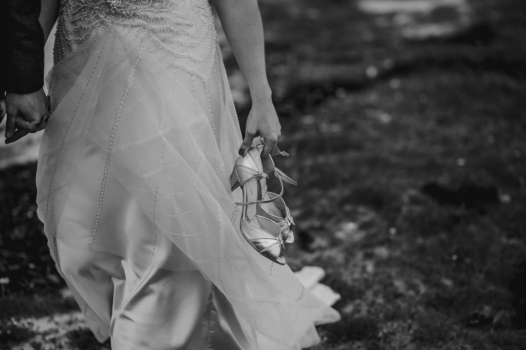 close up of bride holing she shoes and walking