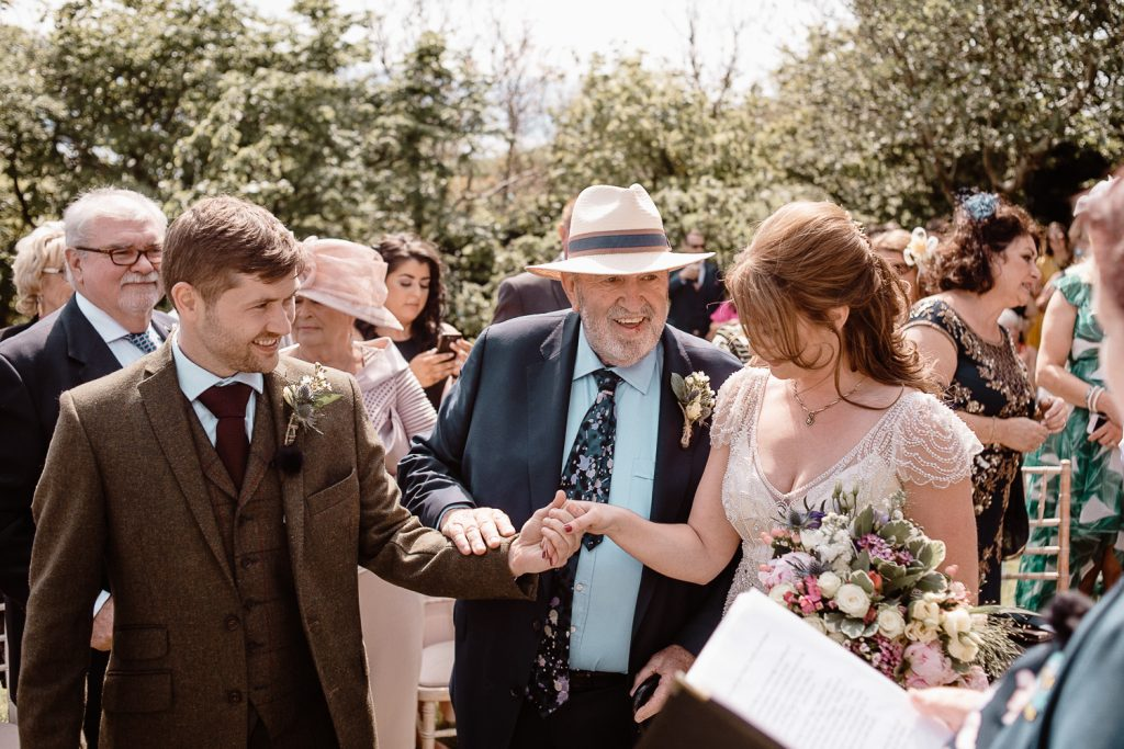 brides father gives her hand to groom