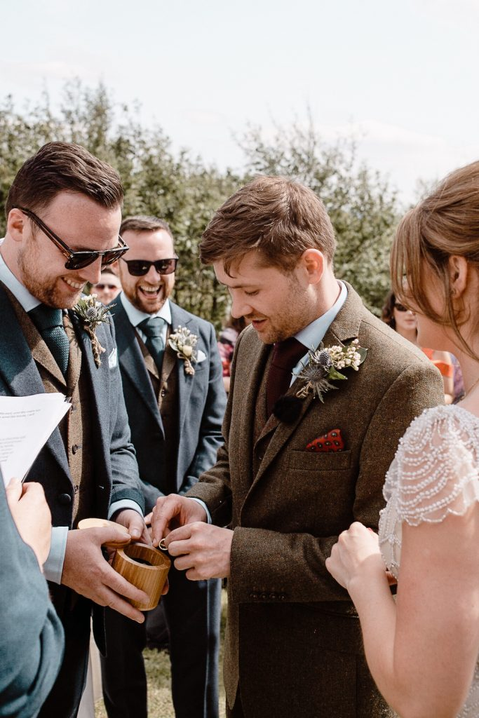 groom getting the wedding ring from best man
