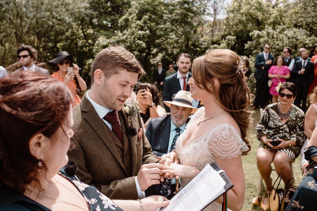 groom putting ring on bides finger