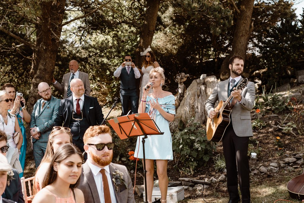 guests singing at wedding outside