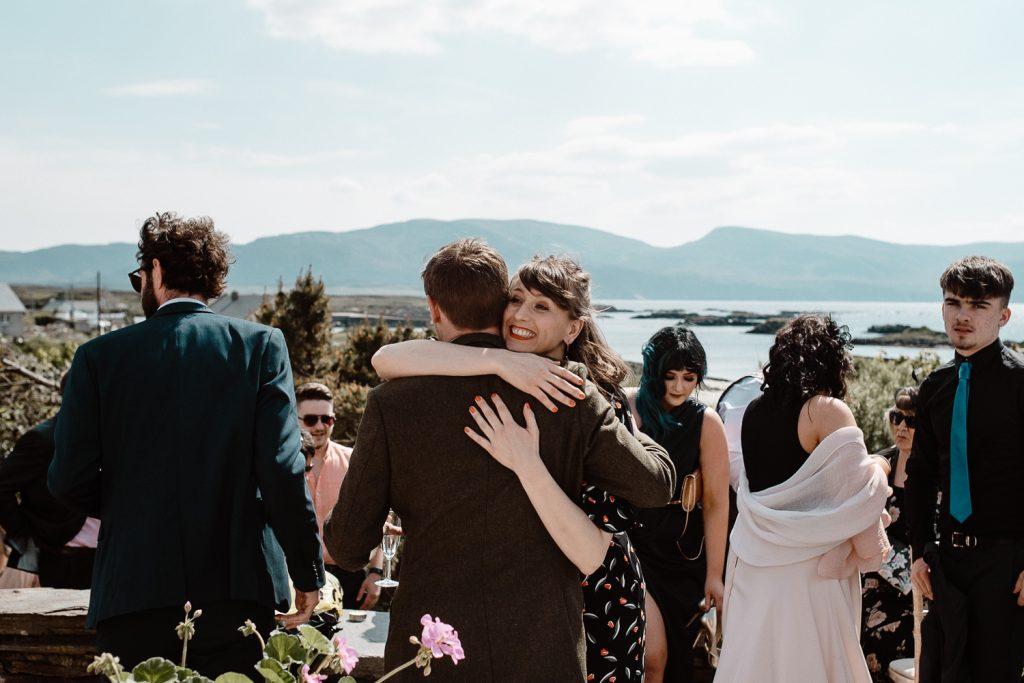 groom hugging guests