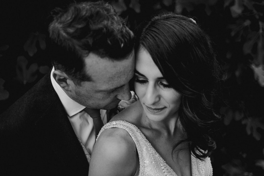 close up groom hugging into brides face