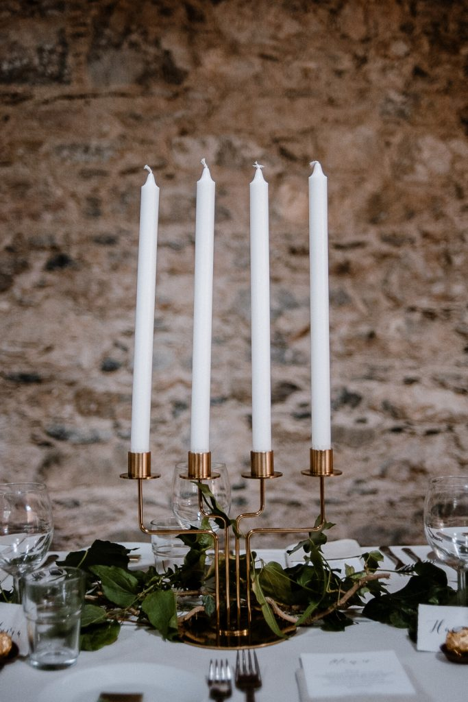 long white candles in gold holder