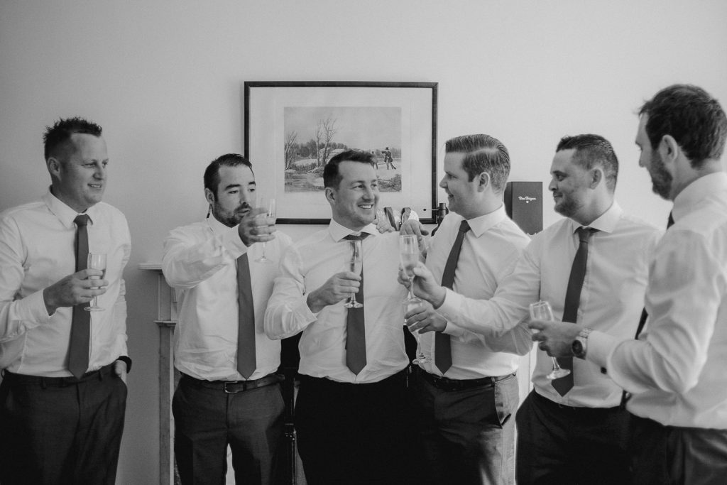 groomsmen and groom toasting a drink