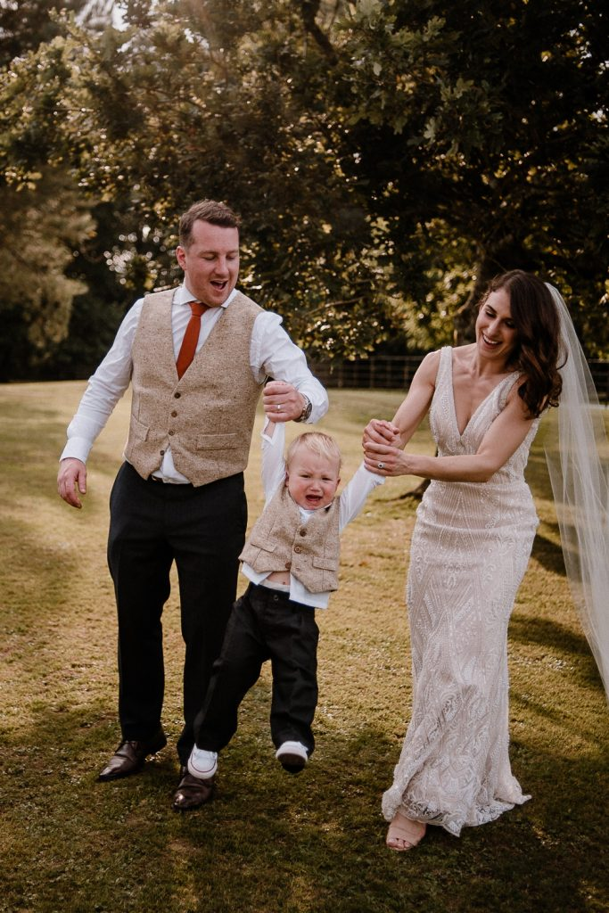 bride and groom swinging their son and he cries