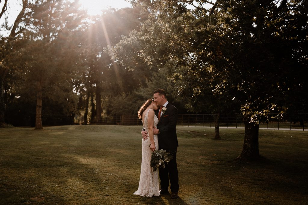 sunset bride rests head on grooms shoulder