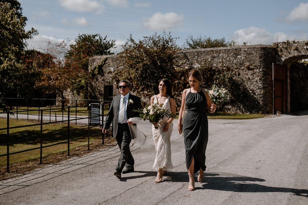 Bride walking to service with father at Blackwater castle wedding