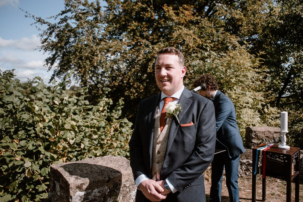 Groom smiles as he sees the bride for the first time