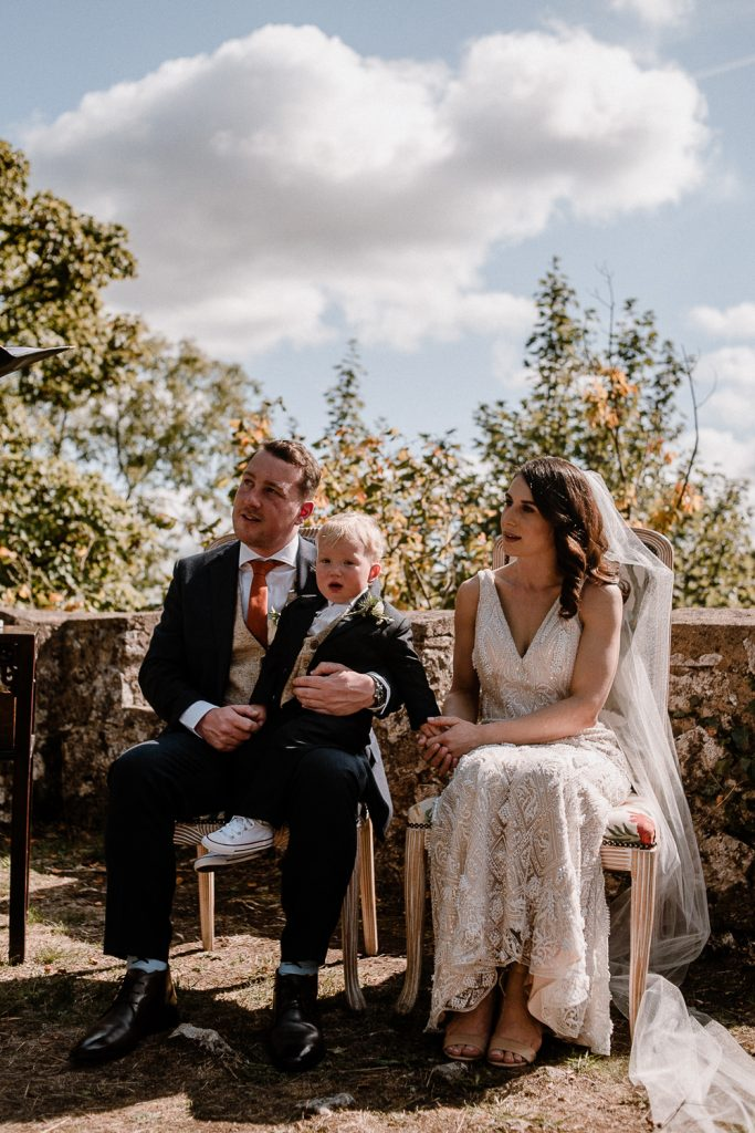 son sits on grooms knee