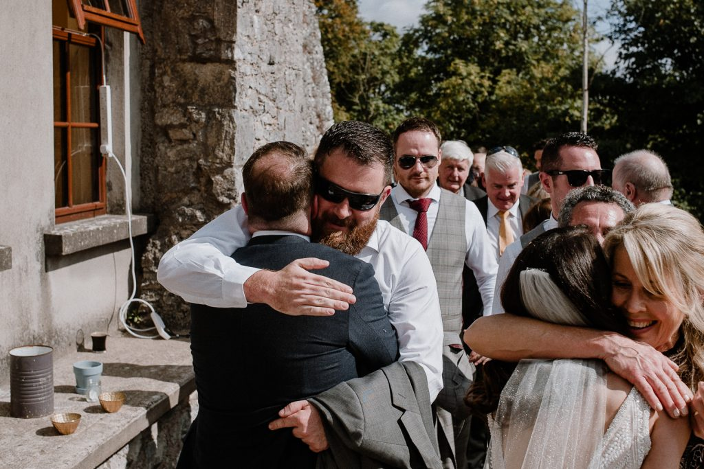 groom hugs wedding guests
