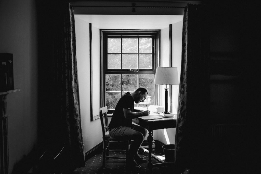 Groom writing speech at window light