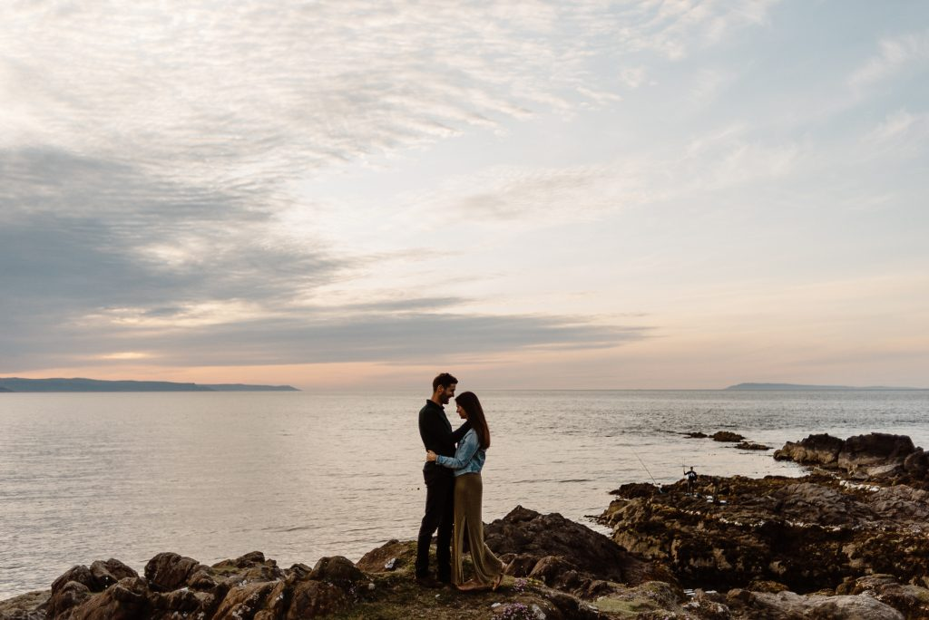 couple standing on rock at sunset