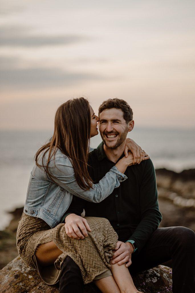 girl kisses man side of face