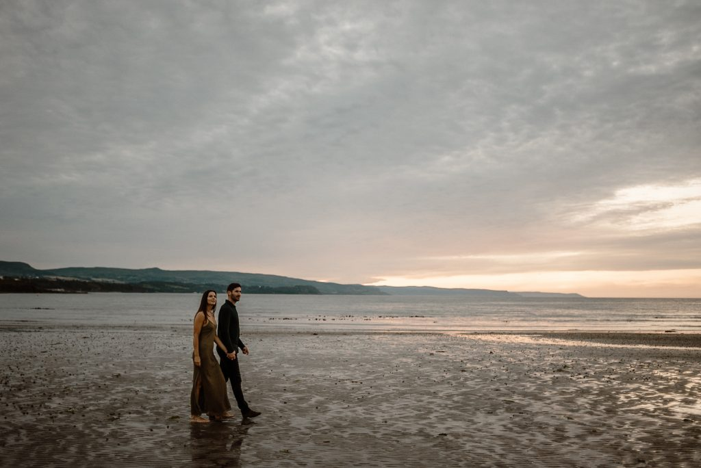 couple walking on a beach at sunset