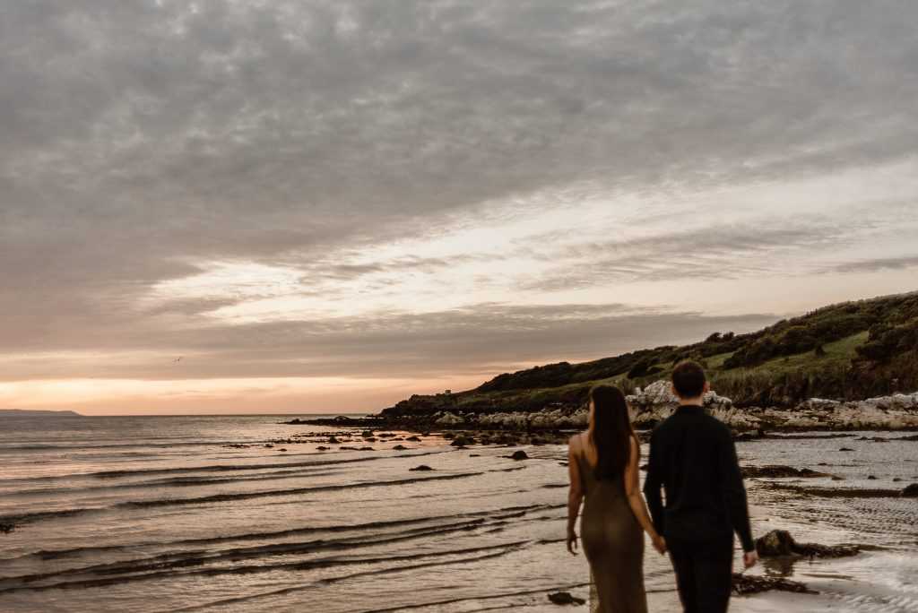 couple walking beside the sea at sunset