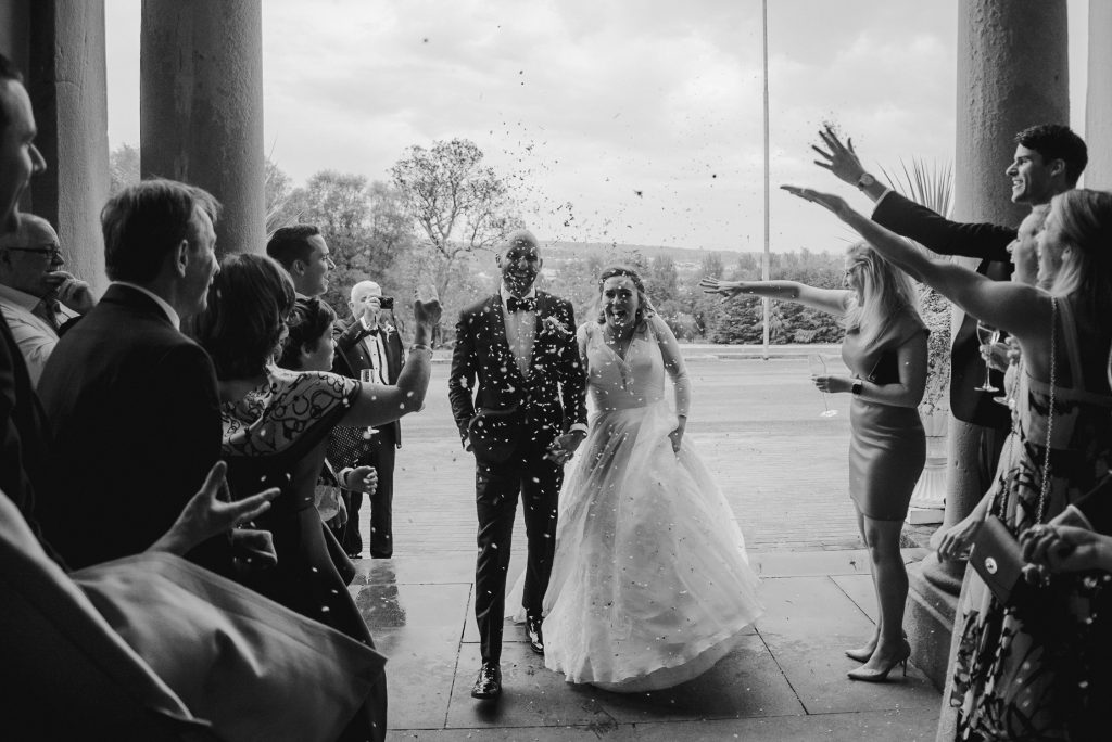 bride and groom and guests throwing confetti