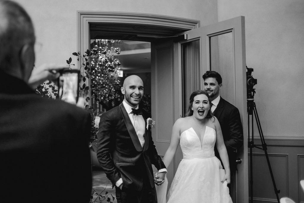 bride and groom walk into reception room