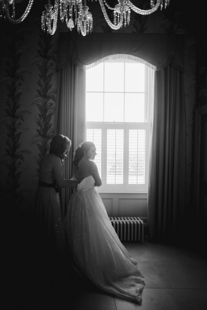 bride and bridesmaid standing by large window