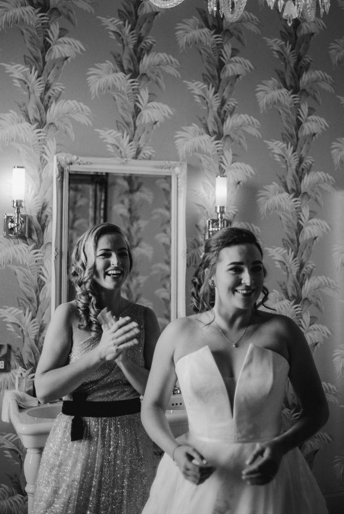 bride and bridesmaid looking in the mirror